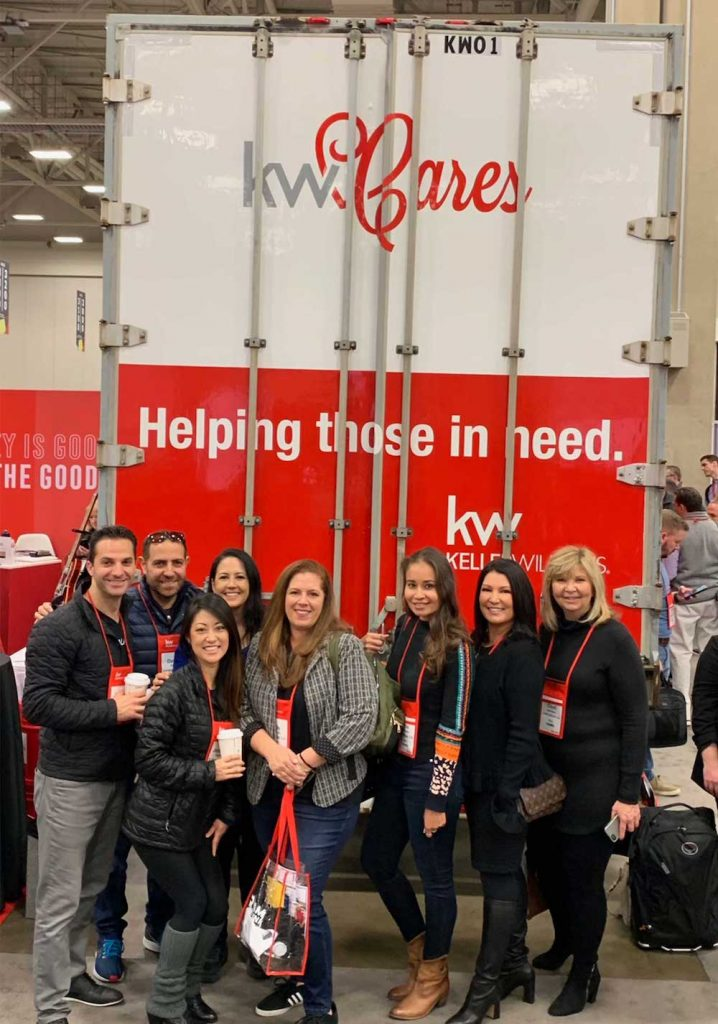 Elaine Ross with the KW Coastal Properties team in front of a KW Cares Banner